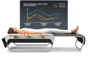 A patient is laying on the CERAGEM bed and a graph above the patient shows their alignment.